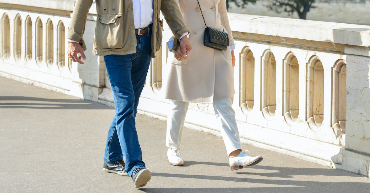 Couple seen from the waist down holding hands and walking across a bridge in Europe