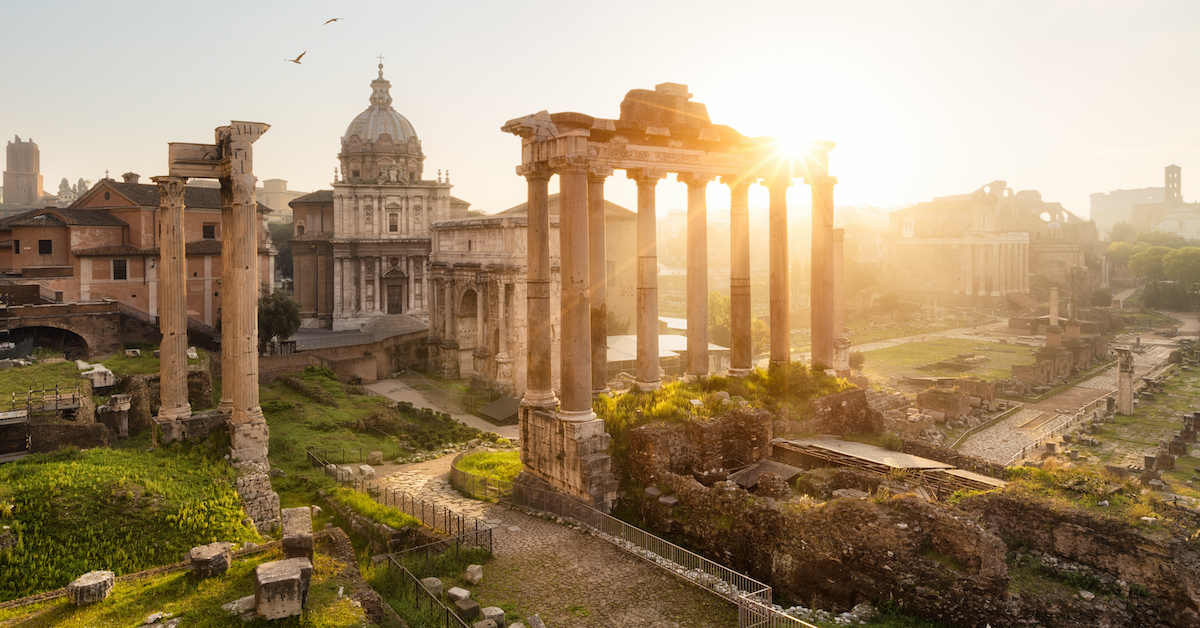 Sun shining over marble columns and a domed stone building in the Ancient Forum of Rome, one of the best family vacations with teens