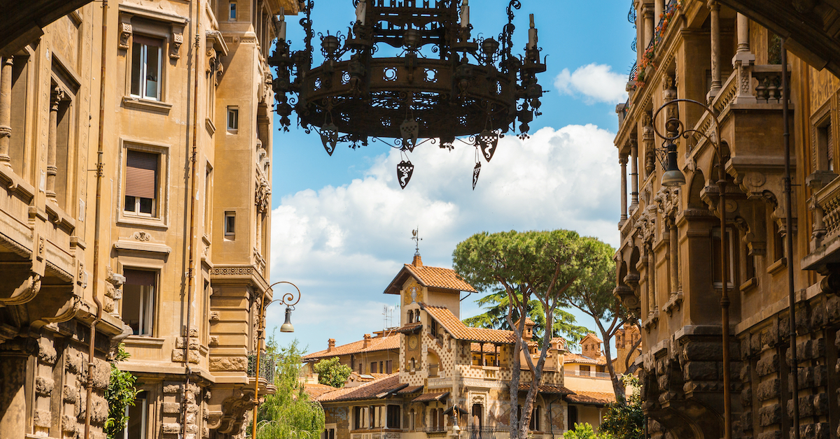Metal chandelier hanging from an archway leading to the intricate stone buildings of Quartiere Coppede in Rome, Italy